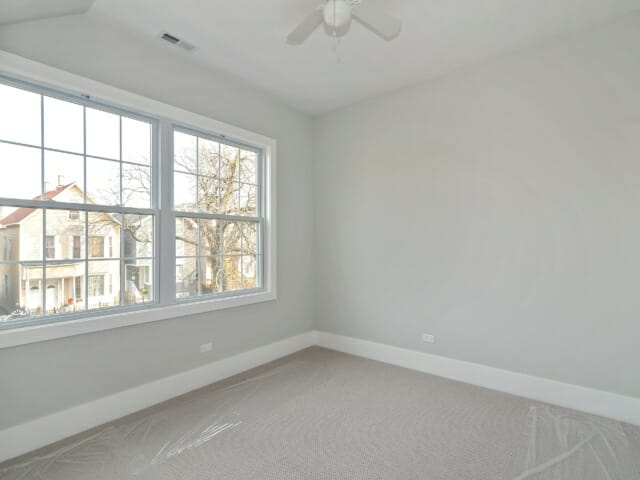 Gut renovated bedroom with carpet, grey walls, painted white trim and two large windows
