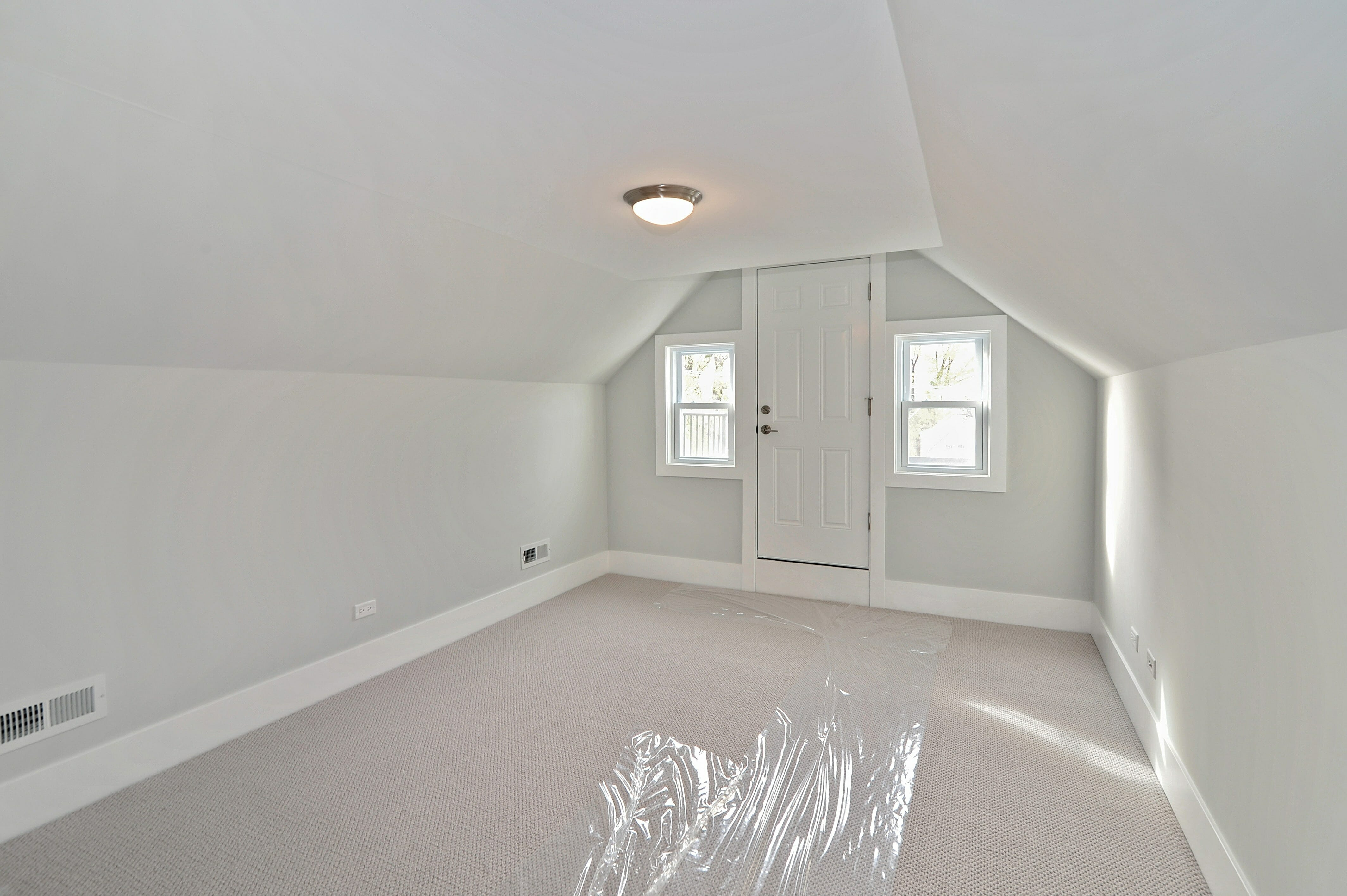 Gut renovated lofted attic with carpet and rear exit door