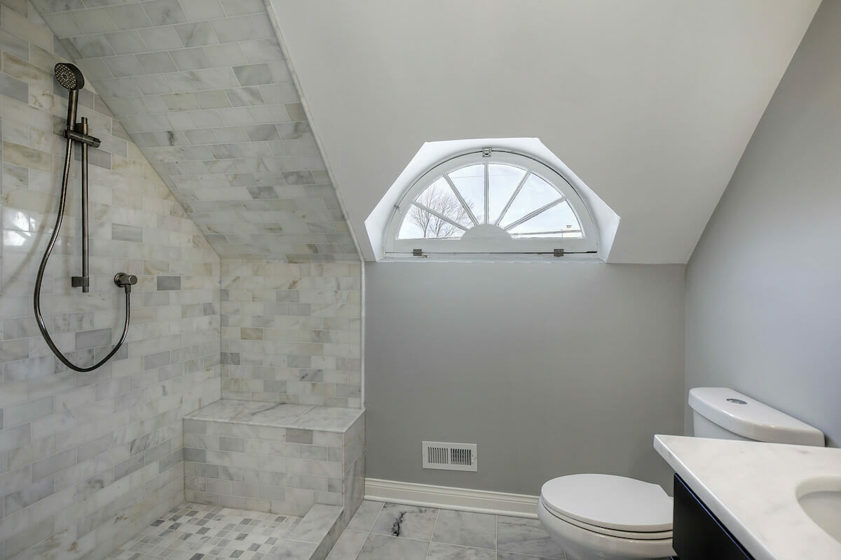 Gut renovated bathroom with marble floor and white tile
