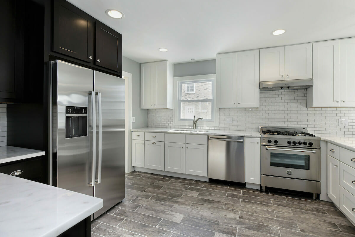 Gut renovated gourmet kitchen in a single family home with stainless appliances, white shaker cabinets, white marble countertops, white ceramic subway tile backsplash, and ceramic wood flooring