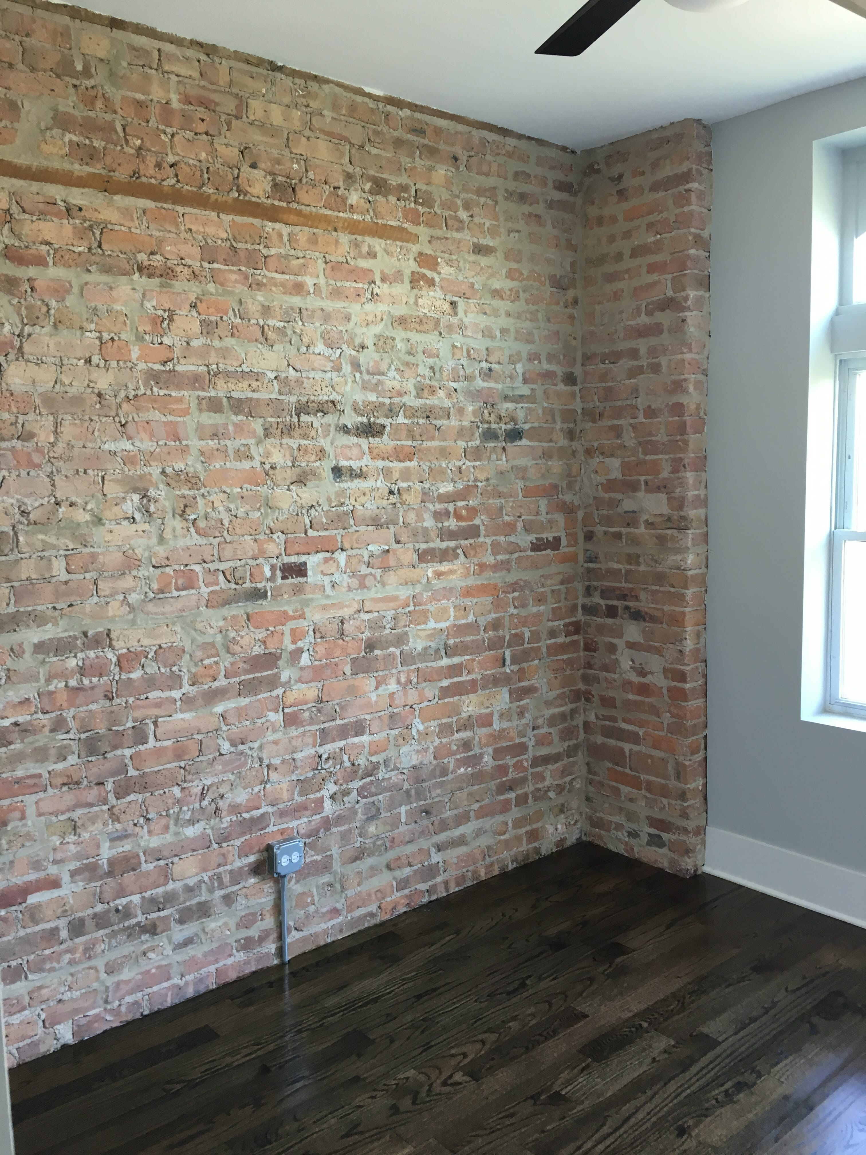 Gut renovated apartment bedroom with dark stained hard wood floors and exposed brick wall