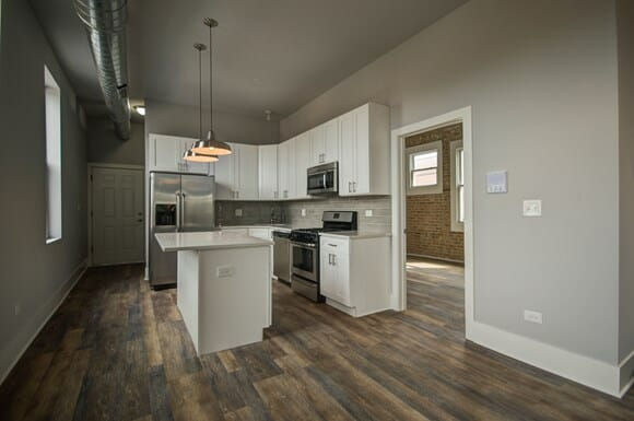Gut renovated apartment kitchen with white shaker cabinets, white quartz countertops, GE stainless appliances, and large island.