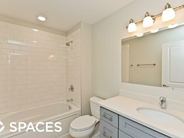 Renovated apartment bathroom with white ceramic subway tile, grey shaker cabinets and white quartz countertops