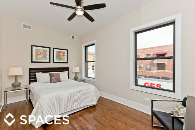 Renovated apartment bedroom with refinished hard wood floors and can lights furnished with traditional furniture