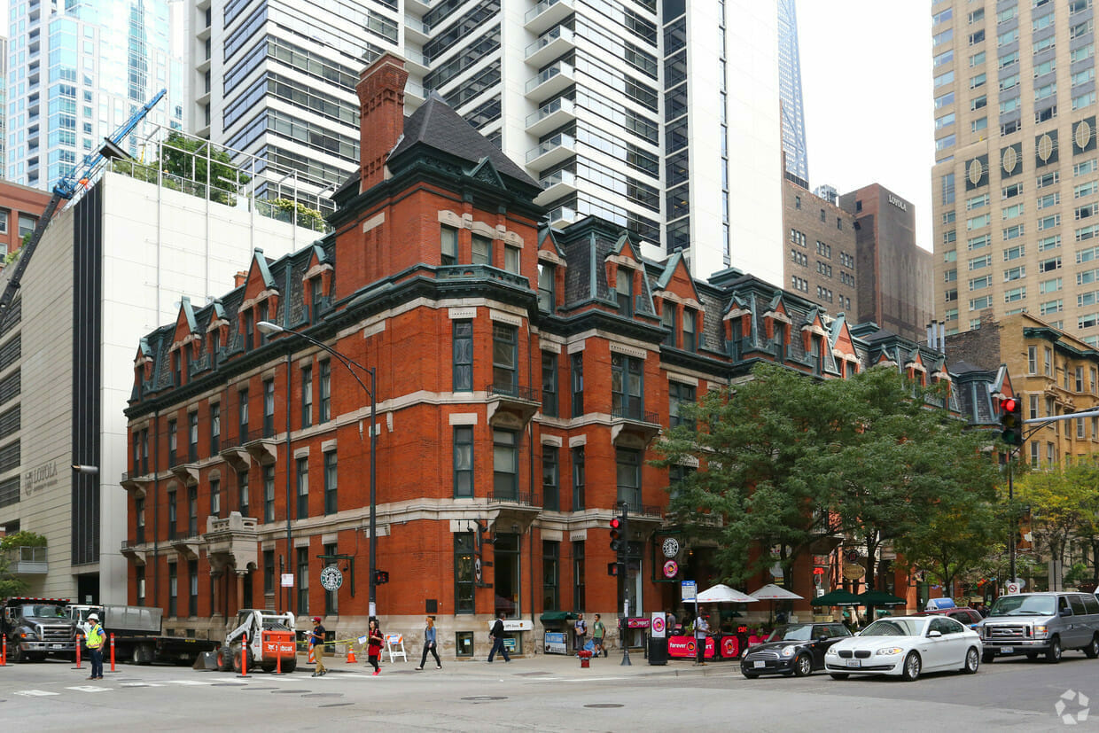 Exterior facade of 4 story apartment building in Chicago with red brick, limestone banding, and a mansard roof with copper gutters featuring a 3F apartment value add renovation