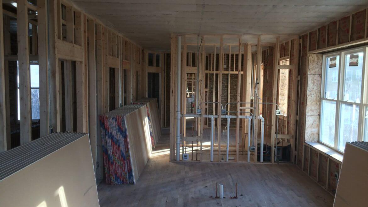 Rough framed apartment unit with exposed studs, PVC plumbing, conduit, insulation, and wood studs.